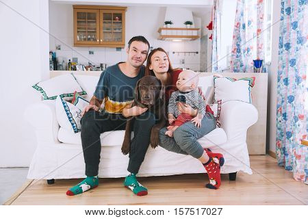 Happy parents with baby and dog on the couch at home interior. Lifestyle family and togetherness concept. Portrait a young playful family at home.