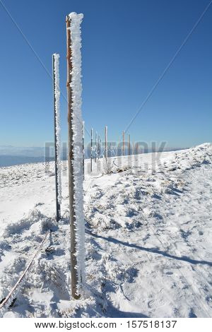 Wooden pillars covered with icicles in long row on the top of the mountain necessary assistance to skiers in foggy winter days vertical orientation