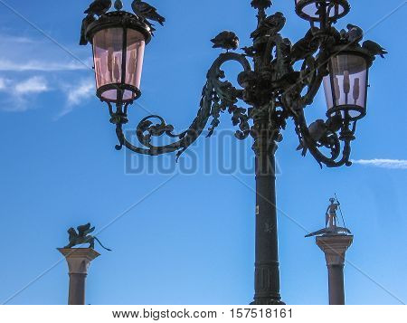 Details of Venice. San Marco square in Venice with San Marco lion statue and its famous street lamp close up.