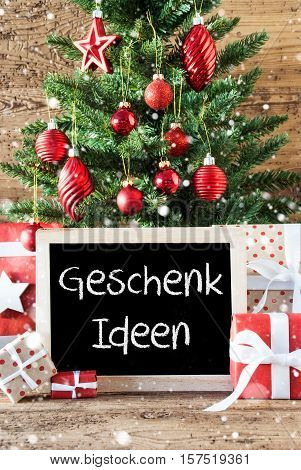 Chalkboard With German Text Geschenk Ideen Means Gift Ideas. Colorful Christmas With Tree With Balls And Snowflakes. Gifts Or Presents In The Front Of Wooden Background.