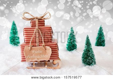 Sleigh Or Sled With Christmas Gifts Or Presents. Snowy Scenery With Snow And Trees. White Sparkling Background With Bokeh Effect. Label With German Frohe Weihnachten Means Merry Christmas