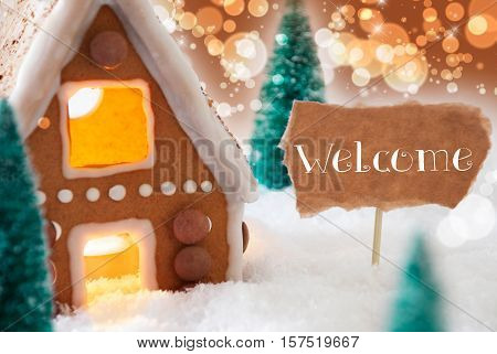 Gingerbread House In Snowy Scenery As Christmas Decoration. Christmas Trees And Candlelight For Romantic Atmosphere. Bronze And Orange Background With Bokeh Effect. English Text Welcome