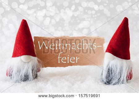 German Text Weihnachtsfeier Means Christmas Party. Christmas Greeting Card With Two Red Gnomes. Sparkling Bokeh Background With Snow. English Text Seasons Greetings