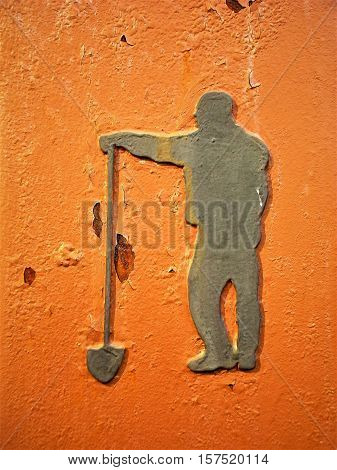 Silver colored metal stencil of a workman standing with a shovel on weathered orange background.