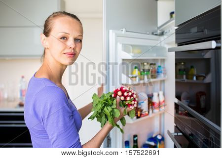 Pretty, young woman taking fresh vegetables from her fridge - being on a gluten free vegan diet does not seem to be a problem for her (shallow DOF; color toned image)