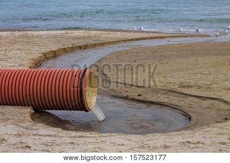 environmental pollution on the beach. Waste pipe or drainage polluting environment. Birds drink waste water
