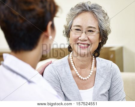 senior asian woman having a pleasant conversation with her family doctor happy and smiling