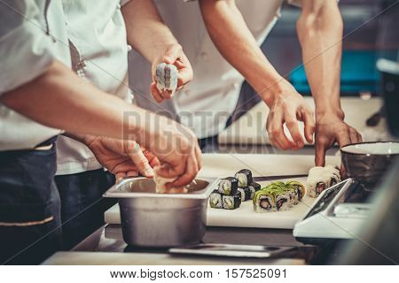 Three cooks in hotel or restaurant kitchen decorating dish. They are working on maki rolls. Preparing sushi set. Only hands