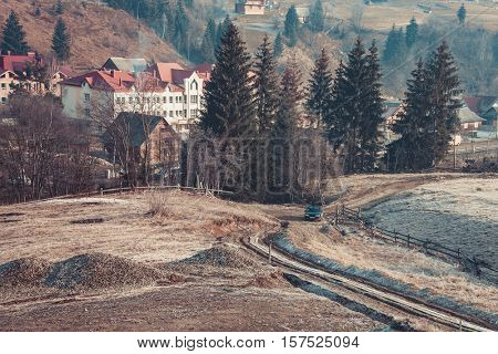 Beautiful autumn in mountain village. Car driving on a country road. Pine trees on the sides. Carpathians, Ukraine, Europe. Exploring beauty world