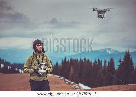 Young man in green jacket operating a drone using a remote controller. Ski resort in the background, winter landscape with pine tree forest and mountains. Bukovel, Carpathians, Ukraine, Europe.