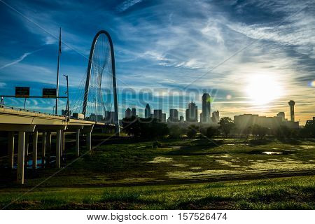 Dallas Texas USA Skyline Cityscape morning sun rays over the city with Reunion Tower and Office buildings and the Margaret Hunt Hill Bridge to the left