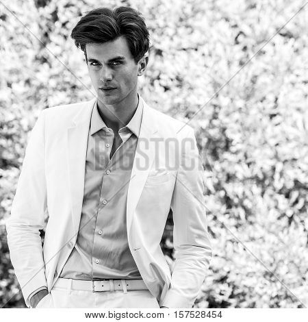 Black-white portrait of young handsome fashionable man in white suit against nature background.