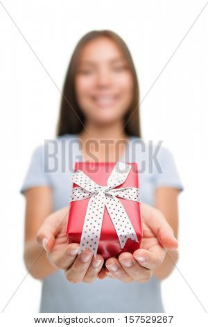 Woman giving red gift box as Christmas or birthday gifts isolated on white background. Holiday season shopping concept, lady presenting cute decorated package in studio.