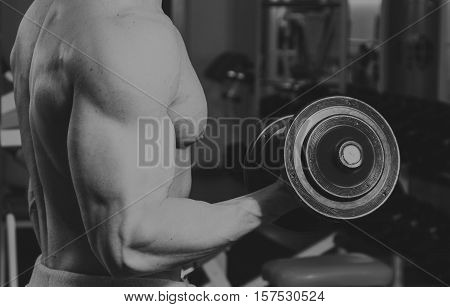 Workout at the fitness club. A strong man in the gym, black and white photo.