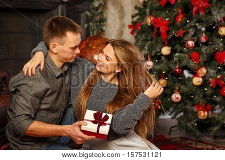 Loving couple and Christmas. Man gives a girl a Christmas gift. They sit on the floor near the fireplace. In the background a beautiful Christmas tree.