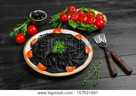 Spaghetti with ink of a cuttlefish. Ingredients for spaghetti with cuttlefish ink herbs thyme rosemary black olives lettuce. Spaghetti with cuttlefish ink decorated with cherry tomatoes.