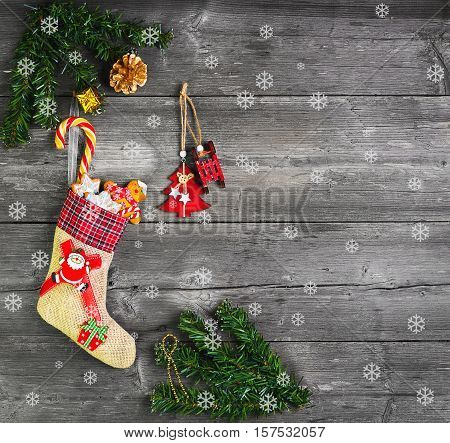 Christmas sock with presents. Christmas decoration stocking and toys hanging over gray rustic wooden background. The socks of burlap Christmas sweets gifts cakes. Christmas snowflakes. Top view
