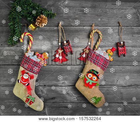 Christmas two sock with presents. Christmas decoration stocking and toys hanging over gray rustic wooden background. The socks of burlap Christmas sweets gifts cakes. Christmas snowflakes. Top view