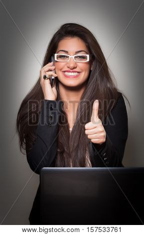 Successful Smiling Young Businesswoman wearing white glasses talking to phone and gives Thumbs Up on grey background