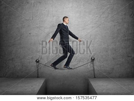 A businessman walking on a drawn tightrope over the gap, on a gray background. Overcoming the obstacles. Difficulties with the business venture.