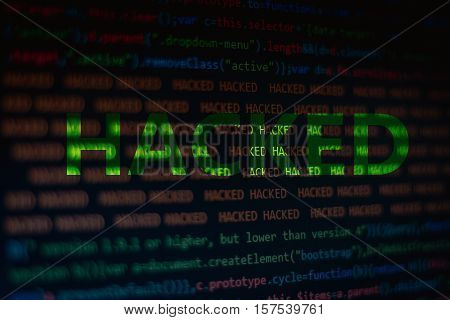 Programming abstract - source code and binary code on display of software developer and a HACKED word