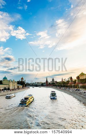 Three floating motor ship on the Moscow River near the Kremlin embankment. A beautiful cloudy sky at sunset