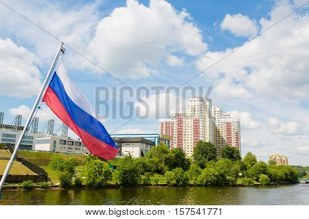 Russian flag on the background of the suburbs of Moscow on Moscow River. Khimki Region, Russia