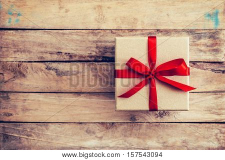 Brown Gift Box On Wooden Background. Vintage Gift Box On Wooden Background. Gift Box With Red Ribbon