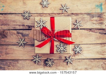 Brown Gift Box And Snowflakes On Wooden Background. Vintage Gift Box On Wooden Background. Gift Box