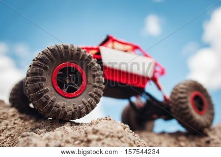 Rc crawler outside, view from below. Red and white toy suv on rocky terrain, blue sky on background, free space