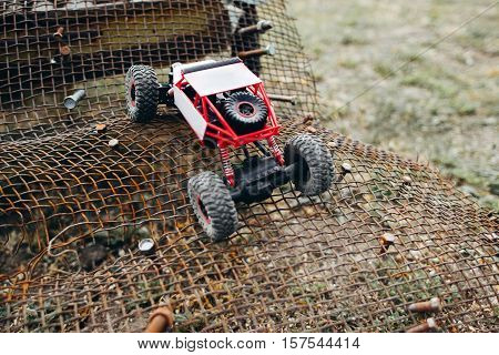RC crawler riding rough surface og grille. Toy suv overcoming metal lattice rises, close-up, free space. Adult leisure , competition of controlled toys outdoor poster