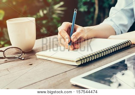 Female Hand With Pencil Writing On Notebook. Woman Hand With Pencil Writing On Notebook At Coffee Sh