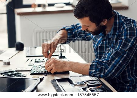 Laptop disassembling with screwdriver, side view. Engineer fixing broken computer motherboard. Electronic repair shop, technology development concept