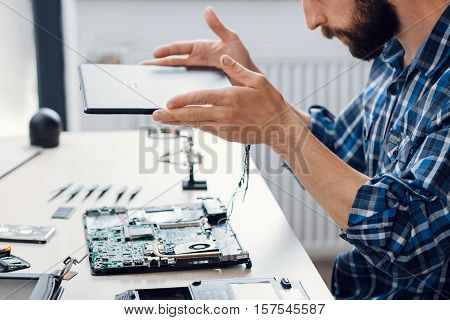 Laptop disassembling at electronic repair shop. Side view on bearded engineer separating computer from case. Electronic renovation, business, occupation concept