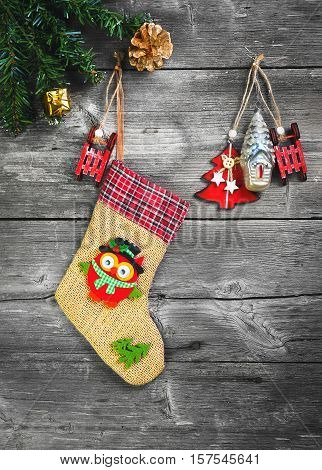 Christmas decoration stocking and toys hanging over gray rustic wooden background. The socks of burlap Christmas sweets gifts cakes. Top view