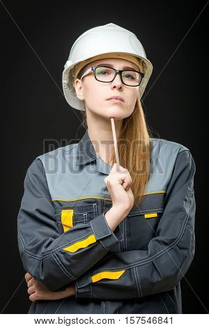 portrait of a young female worker on the black background
