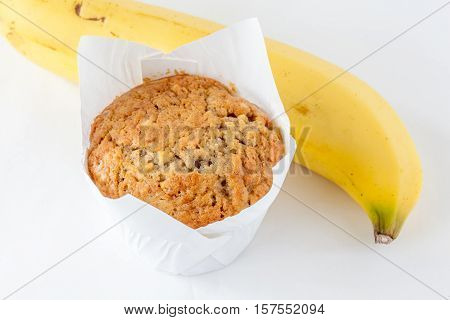 A cup of tasty banana muffin and the key ingredient ripe banana.