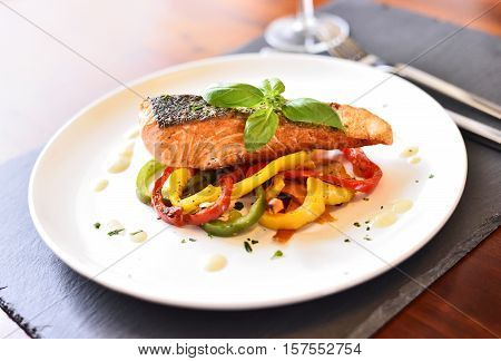 Delicious salmon filet and red bell pepper vegetables on a white plate. Healthy meal, decorated with basil leaf.