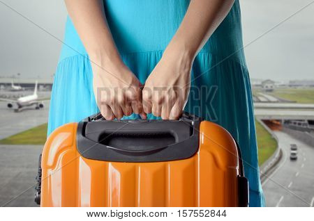 Woman In Blue Dress Holds Orange Suitcase In Hands On Airport Background