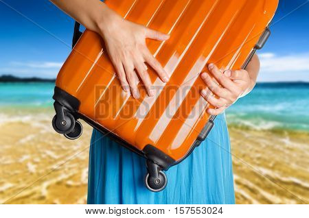 Woman In Blue Dress Holds Orange Suitcase In Hands On The Beach Background