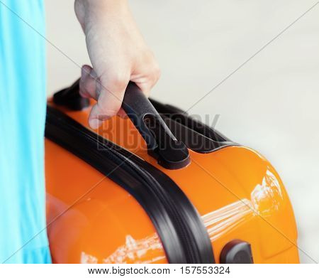 Woman In Blue Dress Holds Orange Suitcase In Hand