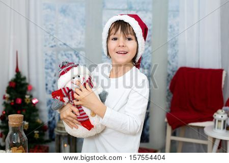 Christmas Portrait Of Cute Little Preschool Boy, Eating Cookies And Playing With Snowman On A Winter