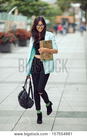 Asian student or school girl street portrait. Woman smiling and walking outside with backpack and book in casual business suite against blurred city space. Beautiful young mixed race Asian Caucasian woman.