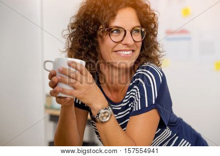 Portrait of a middle aged woman at the office drinking coffee