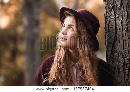 Stylish teen girl 14-16 year old wearing felt hat and winter jacket over nature background outdoors. Looking up. Autumn season.