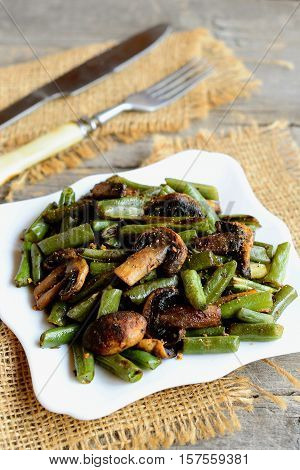 Delicious fried green beans with mushrooms and spices on a plate, fork, knife, burlap on old wooden background. Warm green beans and mushrooms salad. Healthy vegetarian food. Vintage style. Closeup