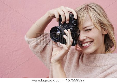 Young blond Beautiful photographer focusing camera smiling