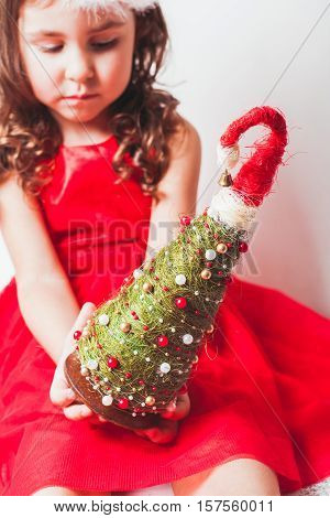 Girl holds in her hands handmade decor - Christmas tree from sisal and beads