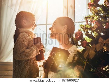 Merry Christmas and Happy Holidays! Cheerful mom and her cute daughter girl exchanging gifts. Parent and little child having fun near Christmas tree indoors. Morning Xmas. Portrait family close up.