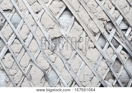 Crumbling obsolescent wooden wall with insulation made of clay. Abstract texture background.